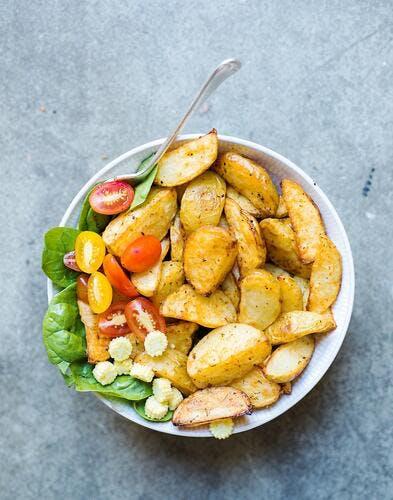 Pommes de terre rôties, salade épinards, tomates et mini-maïs
