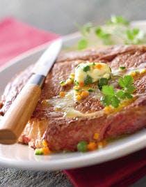 Entrecôte grillée, beurre aux herbes et pommes de terre sous la cendre