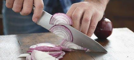 Émincer un oignon rouge avec un couteau de chef